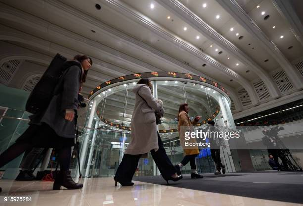 Visitors walk past an electronic ticker standing above the trading floor at the Tokyo Stock Exchange , operated by Japan Exchange Group Inc. , in...