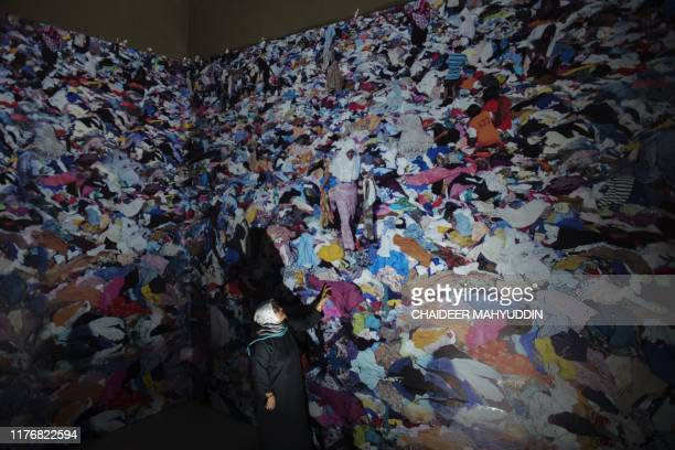 Visitors walk past an exhibit showing images of aid relief at the Aceh Tsunami Museum in Banda Aceh on October 19 where the museum serves as a...