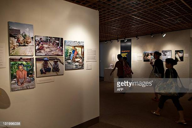 Visitors walk past an exhibition of photographs taken during fieldwork in Indonesia by S Ann Dunham US President Barack Obama's late mother at a...