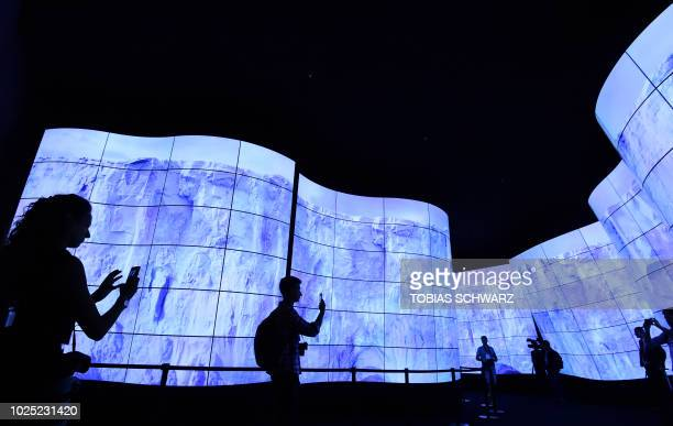 Visitors walk past at an OLED television installation at the booth of LG during a preview day for the IFA the world's leading trade show for consumer...