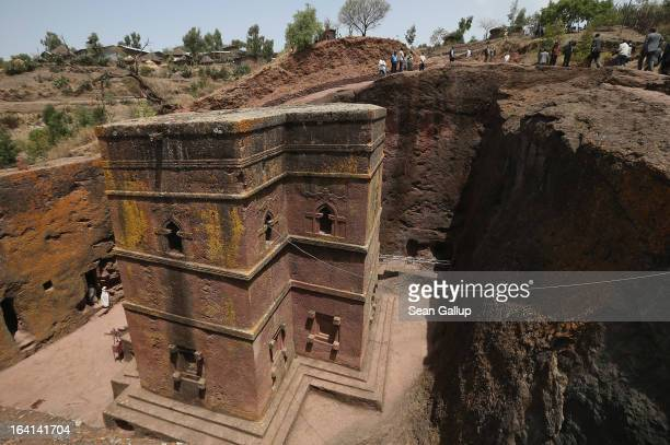 Visitors walk past Bete Giyorgis also called St George's Church at the Lalibela holy sites on March 19 2013 in Lalibela Ethiopia Lalibela is among...