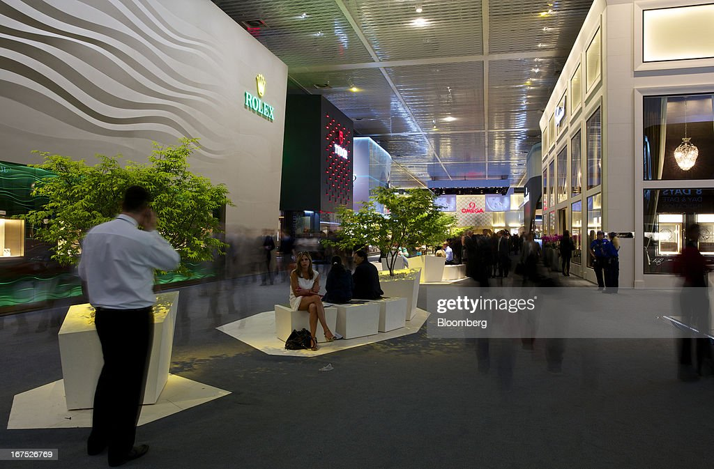 Visitors walk past display halls for Rolex Group, Tudor, and Omega watches during the Baselworld watch fair in Basel, Switzerland, on Thursday, April 25, 2013. The annual fair attracts 2,000 companies from the watch, jewelry and gem industries to show their new wares to more than 100,000 visitors. Photographer: Gianluca Colla/Bloomberg via Getty Images