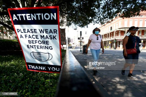 Visitors walk past face mask signs along Decatur Street in the French Quarter on July 14, 2020 in New Orleans, Louisiana. Louisiana Gov. John Bel...
