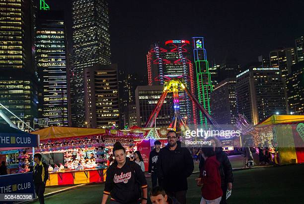 Visitors walk past fairground stalls at the AIA Group Ltd Great European Carnival as the HSBC Holdings Plc headquarters building center rear stands...