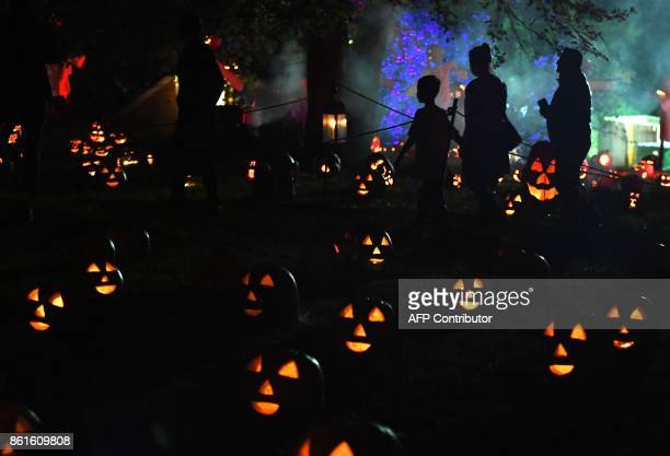 Visitors walk past illuminated pumpkins on display during the Great Jack O'Lantern Blaze at Van Cortlandt Manor in CrotononHudson New York on October...
