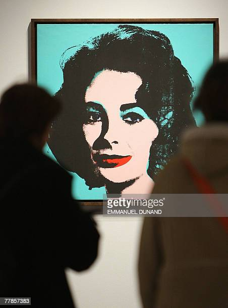 Visitors walk past 'Liz' by US artist Andy Warhol at Christie's auction house before it goes on sale for an estimated bid of 2535 million USD in New...