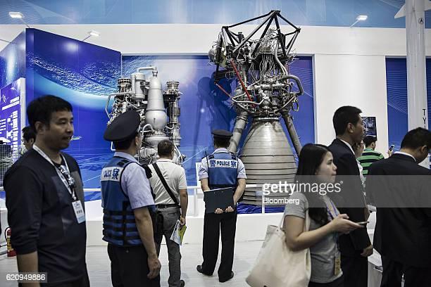 Visitors walk past mockups of rocket engines at the China International Aviation Aerospace Exhibition in Zhuhai China on Tuesday Nov 1 2016 The...