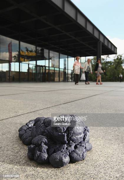 Visitors walk past one of four piles of fake blue horse manure outside the Neue Nationalgalerie art museum on August 7 2012 in Berlin Germany The...