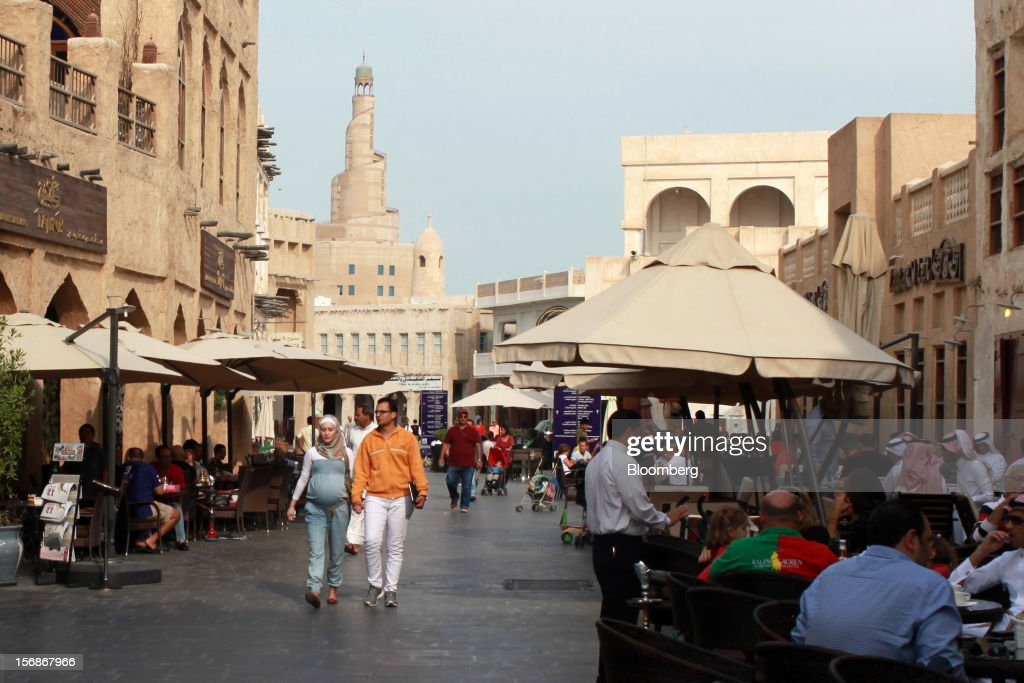 Visitors walk past outdoor restaurants in the Souq Waqif market in Doha, Qatar, on Thursday, Nov. 22, 2012. Qatar Telecom QSC, the country's biggest company by revenue, is seeking a syndicated loan for about $1 billion to refinance existing debt, according to a person with direct knowledge of the deal. Photographer: Gabriela Maj/Bloomberg via Getty Images
