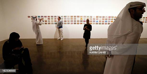 Visitors walk past paintings by Emirati digital artist Ebtisam Abdulaziz on display during part of an exhibition titled Autobiography 2012 in Dubai...