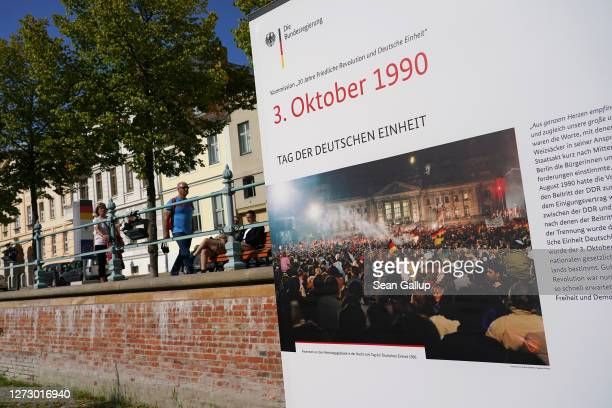 Visitors walk past panels at an outdoor exhibition marking the upcoming 30th anniversary of German reunification on September 17, 2020 in Potsdam,...