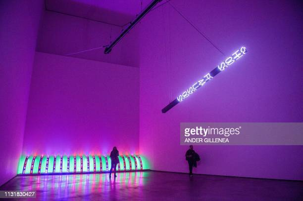 Visitors walk past 'Purple' and 'I woke up naked' by US artist Jenny Holzer during a presentation of the 'Jenny Holzer Thing Indescribable'...