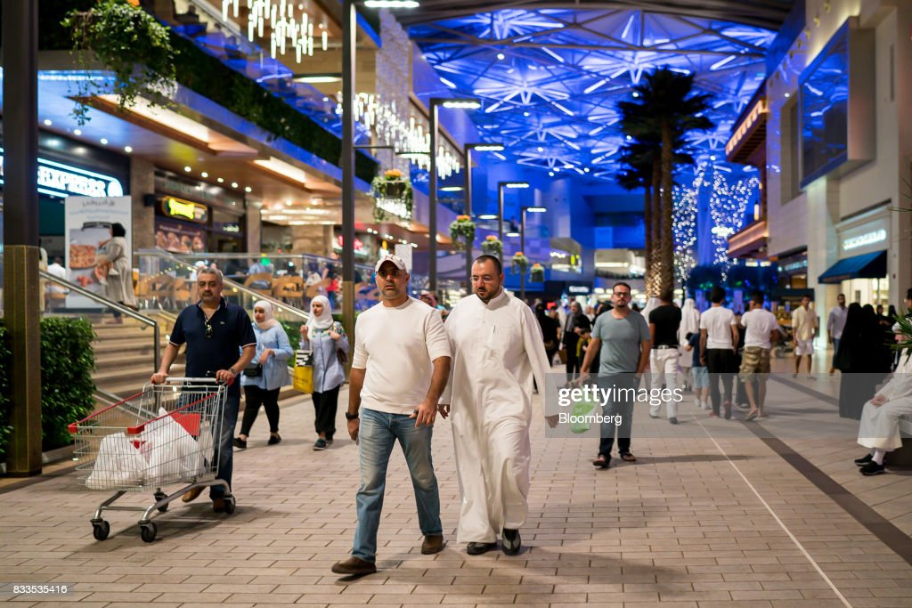 Visitors walk past restaurants and retail stores in Avenues shopping mall in Kuwait City, Kuwait, on Sunday, Aug. 13, 2017. Kuwait will issue a tender to build the estimated $1.2 billion Dibdibah solar-power plant in the first quarter of 2018 as part of the countrys plans to produce 15 percent of power from renewable energy by 2030. Photographer: Tasneem Alsultan/Bloomberg via Getty Images