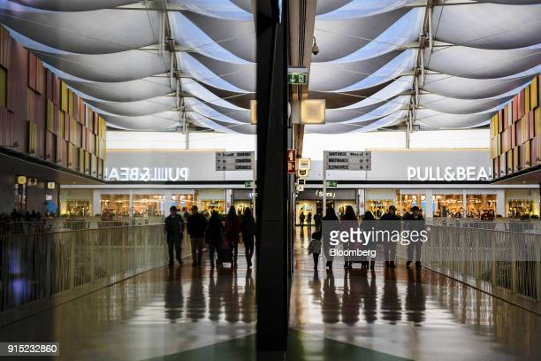 Visitors walk past retail stores in a shopping arcade at the Dolce Vita Tejo shopping mall operated by AXA Real Estate Investment Managers SGR SpA in...