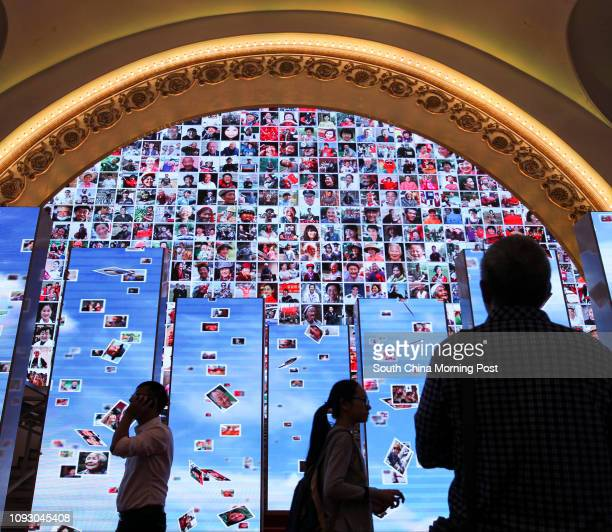 Visitors walk past screens showing smiling faces of Chinese people at a special exhibition celebrating the achievements in the past five years since...