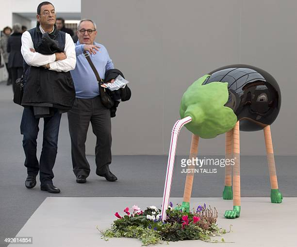 Visitors walk past Sculpture by Darren Bader on display at the Frieze Art Fair in London on October 14 2015 CAPTION