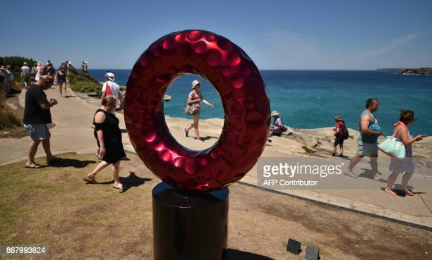 Visitors walk past sculptures on display on Tamarama Beach as part of the Sculpture by the Sea exhibition in Sydney on October 30 2017 Celebrating...