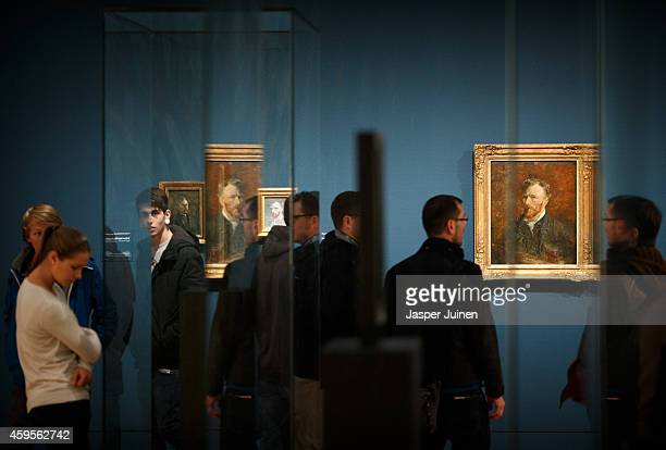 Visitors walk past self portraits of Dutch PostImpressionist painter Vincent van Gogh on the ground floor of the Vincent van Gogh museum on November...