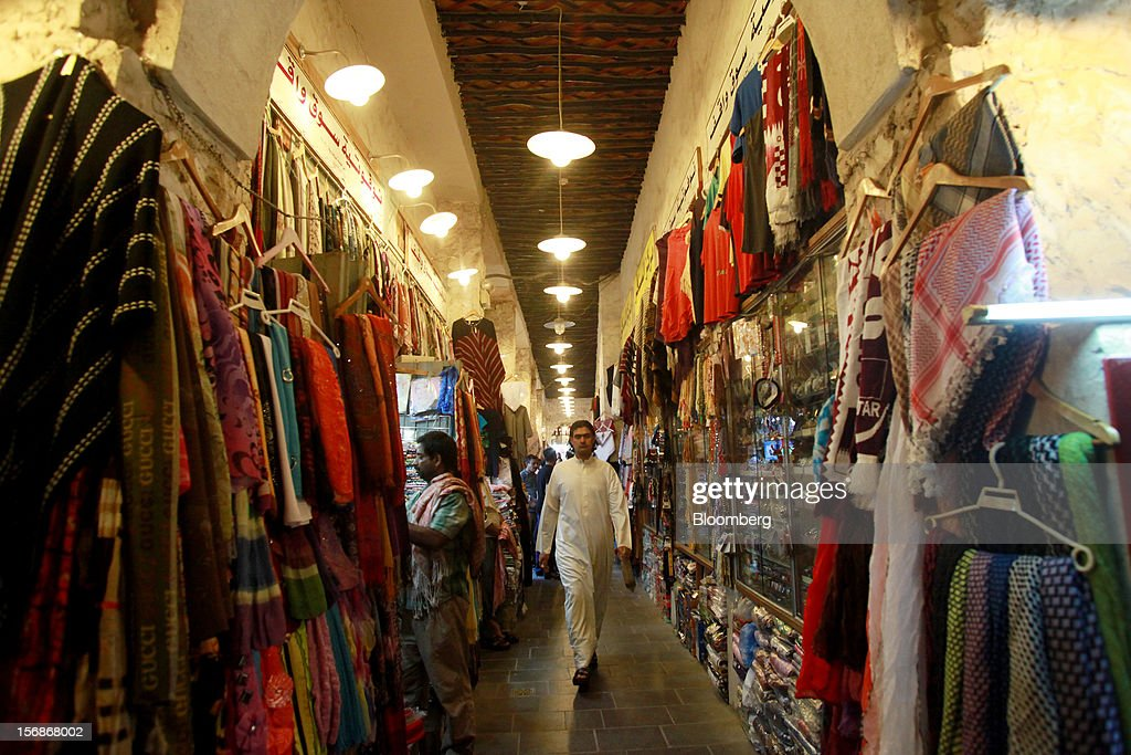 Visitors walk past stores displaying fashion goods inside the Souq Waqif market in Doha, Qatar, on Thursday, Nov. 22, 2012. Qatar Telecom QSC, the country's biggest company by revenue, is seeking a syndicated loan for about $1 billion to refinance existing debt, according to a person with direct knowledge of the deal. Photographer: Gabriela Maj/Bloomberg via Getty Images