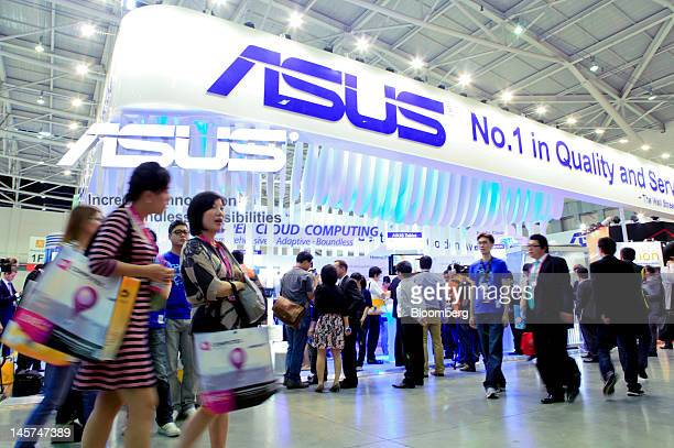 Visitors walk past the Asustek Computer Inc booth at Computex Taipei 2012 in Taipei Taiwan on Tuesday June 5 2012 Computex Taipei 2012 takes place...