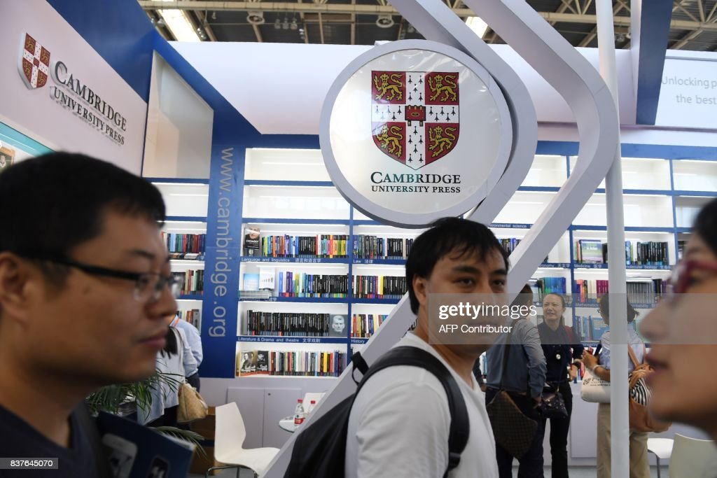 Visitors walk past the Cambridge University Press stand at the Beijing International Book Fair in Beijing on August 23, 2017. A second academic journal has received requests to censor content in China, following an international outcry after Cambridge University Press temporarily agreed to block sensitive articles from another publication under pressure from Beijing. / AFP PHOTO / Greg Baker