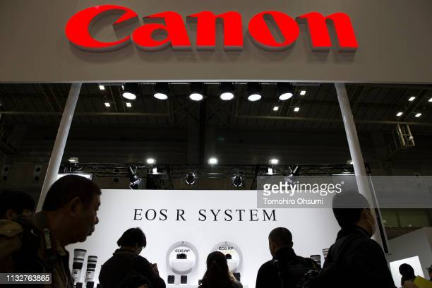 Visitors walk past the Canon Inc. Booth at the CP+ Camera and Photo Imaging Show on February 28, 2019 in Yokohama, Japan. The world premiere show for...