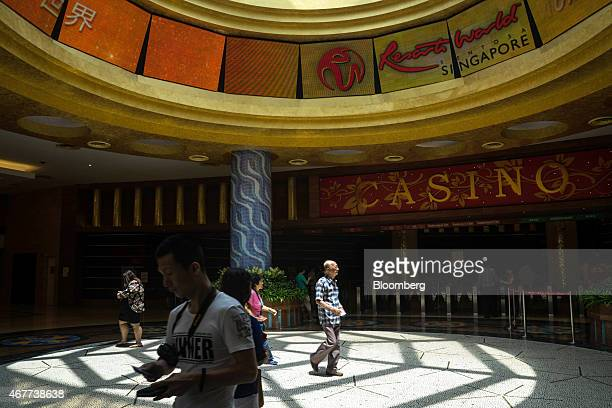 Visitors walk past the casino at Resorts World Sentosa operated by Genting Singapore Plc in Singapore on Thursday March 26 2015 Companies ranging...