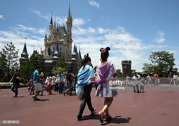 Visitors walk past the Cinderella Castle at Tokyo Disneyland operated by Oriental Land Co in Urayasu Chiba Prefecture Japan on Tuesday July 8 2014...