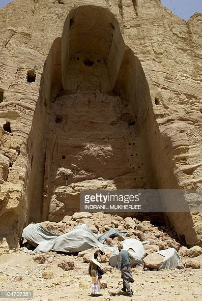 Visitors walk past the destroyed site of one of the historic Buddha statues in Bamiyan 18 May 2002 A meeting is scheduled later this month in...