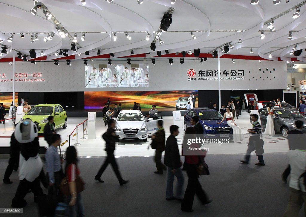 Visitors walk past the Dongfeng Motor Group Co. booth at the Beijing Auto Show in Beijing, China, on Friday, April 23, 2010. The show will be held through April 27. Photographer: Tomohiro Ohsumi/Bloomberg via Getty Images