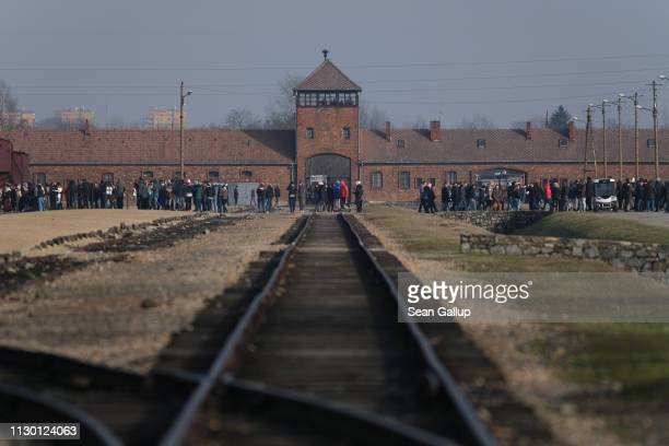 Visitors walk past the entrance gate and original railway tracks, where arriving Jews were sorted between slave labor and the gas chambers, at the...
