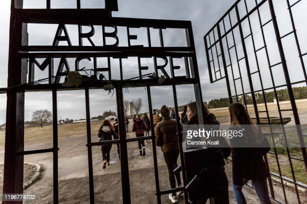 "Visitors walk past the infamous entrance gate that reads: ""Arbeit macht frei"", or ""Work sets one free"" at the Sachsenhausen concentration camp..."