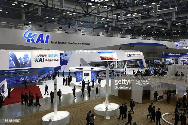 Visitors walk past the Korea Aerospace Industries Ltd. Booth at the Seoul International Aerospace & Defense Exhibition 2013 in Goyang, South Korea,...