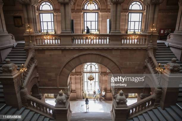 A visitors walk past the Million Dollar Staircase inside the New York State Capitol building in Albany New York US on Wednesday May 22 2019 New York...