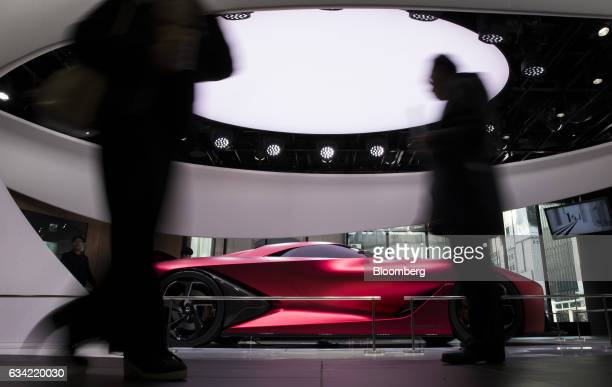 Visitors walk past the Nissan Concept 2020 Vision Gran Turismo concept vehicle displayed at Nissan Motor Co's Nissan Crossing showroom in the Ginza...