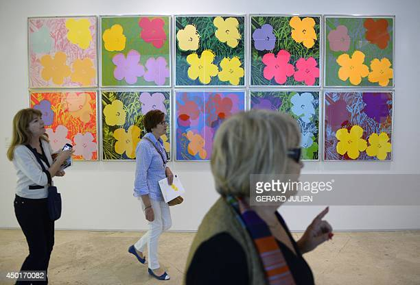 Visitors walk past the painting 'Flowers' by US artist Andy Warhol during an exhibition titled 'Pop Art Myths' at the ThyssenBornemisza museum in...