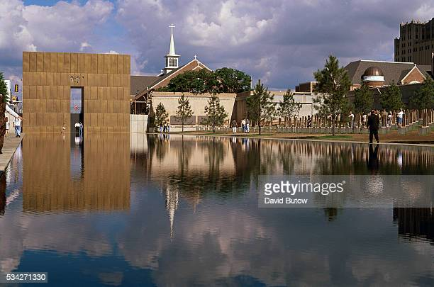 Visitors walk past the reflecting pool and the Gates of Time at the Oklahoma City National Memorial On April 19 Timothy McVeigh exploded a truck bomb...