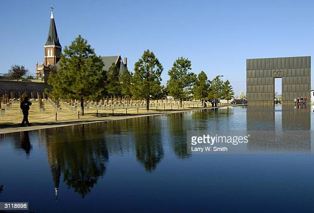 Visitors walk past the reflections from a memorial wall with 903 etched into it the time of the Oklahoma City bombing on March 21 2004 In Oklahoma...