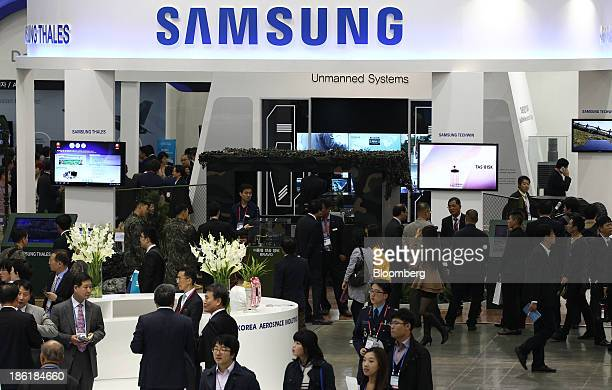 Visitors walk past the Samsung Techwin Co. And Samsung Thales Co. Booth at the Seoul International Aerospace & Defense Exhibition 2013 in Goyang,...
