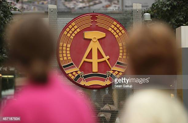 Visitors walk past the state seal of former communist East Germany at an exhibition about 25 years since the fall of the Berlin Wall at the Potsdamer...