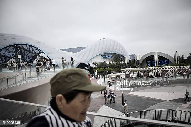 Visitors walk past the Tron Lightcyle Power Run rollercoaster area at Walt Disney Co's Shanghai Disneyland theme park during a trial run ahead of its...
