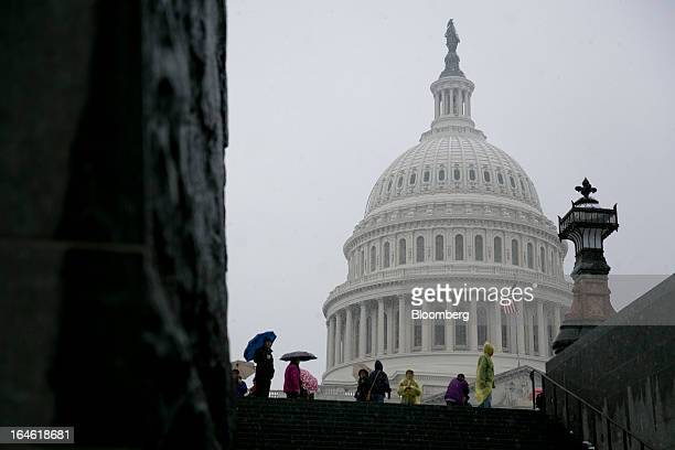 Visitors walk past the US Capitol while holding umbrellas in Washington DC US on Monday March 25 2013 An early spring snowstorm tied up air traffic...