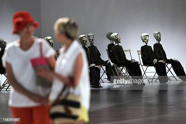 Visitors walk past the work of Swiss Eva Aeppli named Groupe de 13 Group of 13 Amnesty International Tribute to during the exhibition XXL Extra Large...
