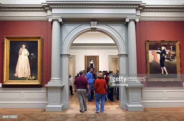 Visitors walk past two paintings by Edouard Manet in the 19thcentury European art galleries at the Metropolitan Museum of Art in New York US on...