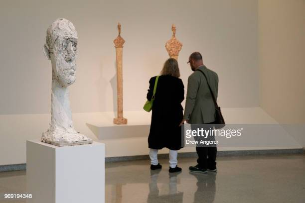 Visitors walk through a retrospective exhibition of work by Swiss sculptor and artist Alberto Giacometti at the Guggenheim Museum June 7 2018 in New...