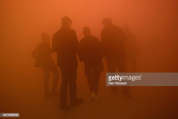 Visitors walk through an installation by artist Ann Veronica Janssens entitled 'yellowblupink' during a press preview at the Wellcome Collection on...