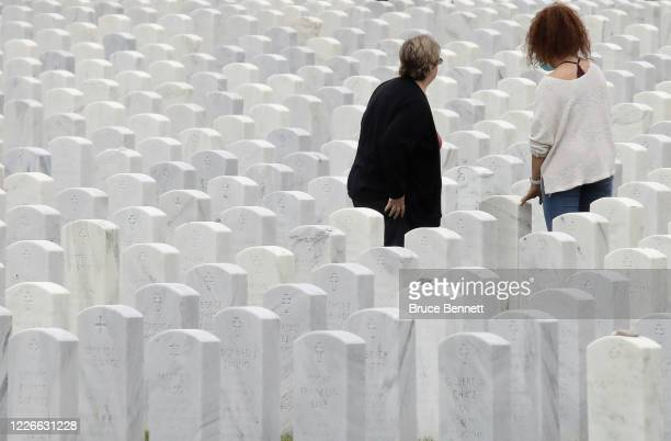 Visitors walk through Calverton National Cemetery on May 23 2020 in Wading River New York Health guidelines due to the coronavirus pandemic is...