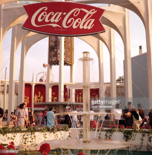 Visitors walk through CocaCola's 'World Of Refreshment' pavilion in Flushing Meadows Park during the World's Fair in Queens New York New York June...