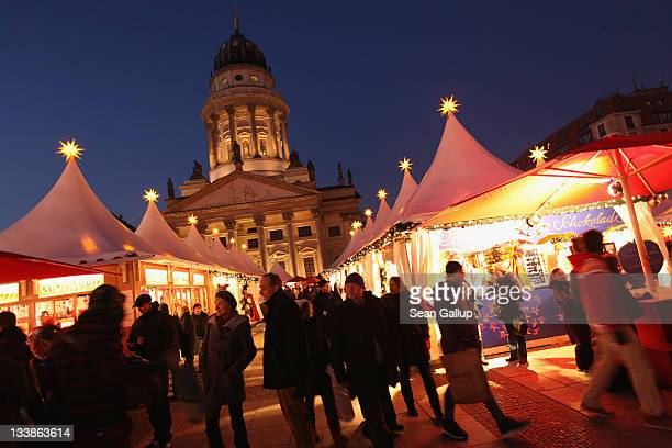 Visitors walk through the Christmas market at Gendarmenmarkt square on the market's opening day on November 21 2011 in Berlin Germany Christmas...