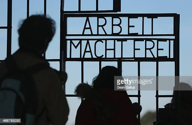 Visitors walk through the infamous 'Arbeit Macht Frei' inscription at the original entrance gate to the former Sachsenhausen concentration camp near...